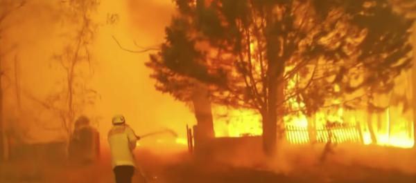A firefighter battles the flames from an Australian wildfire. (Image: YouTube/Screenshot)
