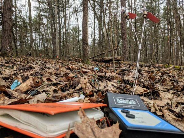 A soil oxygen meter and field book for recording soil oxygen concentrations in the Shale Hills watershed. In the background are soil gas wells for sampling 8-inch and 16-inch soil depths. (Image: CAITLIN HODGES)