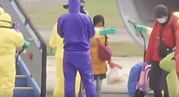 Officers at Indonesia's Batam airport spray passengers with disinfectant as they get off a plane arriving from Wuhan. They were later transferred on a flight to Natuna Island where they are being quarantined for two weeks. (Image: YouTube/Screenshot)