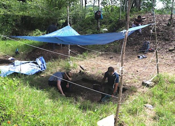 Schroder (left) and Scherer (right) excavate in the ballcourt which they enclosed with a fence to keep away nosy cows. (Image: Charles Golden)