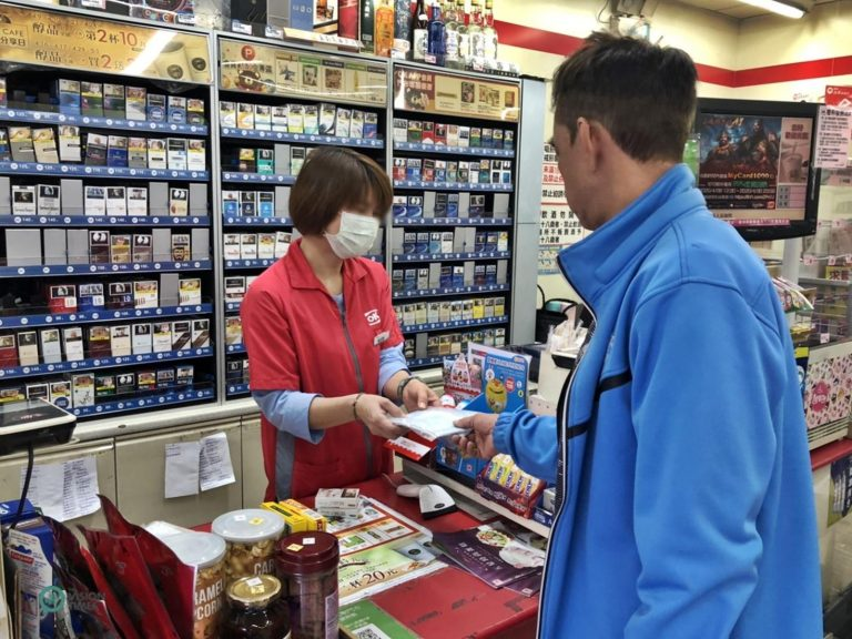 A Taiwan residents picks up the face masks he ordered at a convenience store in Taiwan's Keelung City. (Image: Billy Shyu / Nspirement)