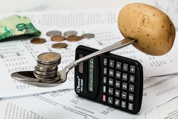 A potato balanced by coins over a calculator showing the importance to manage one's finances wisely.
