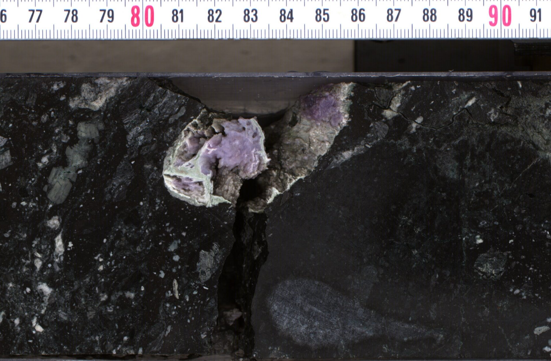 Hydrothermal minerals (silica and feldspar) in cavity within impact melt rock core. (Image: ECORD-IODP Exp 364)