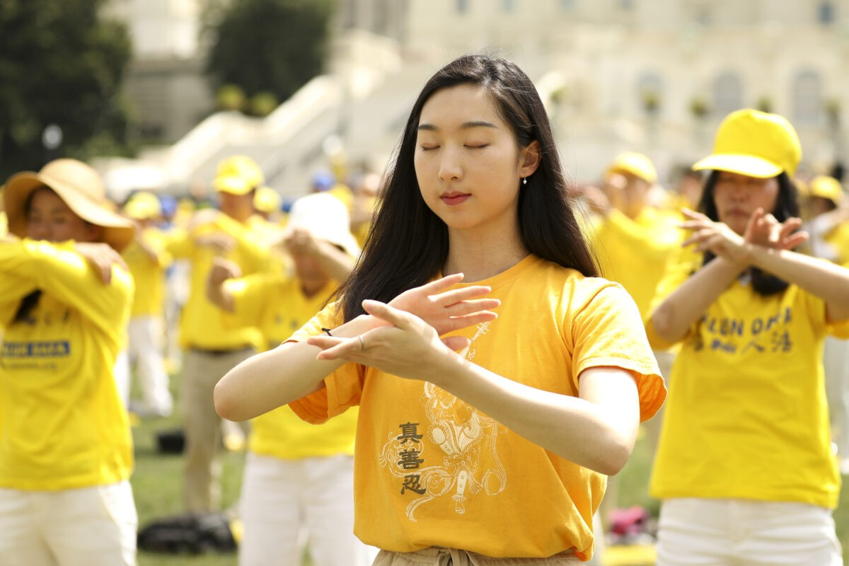 Falun Gong practitioners perform the exercises at a rally commemorating the 20th anniversary of the persecution of Falun Gong in China, on the West Lawn of Capitol Hill on July 18, 2019. (Samira Bouaou/The Epoch Times)
