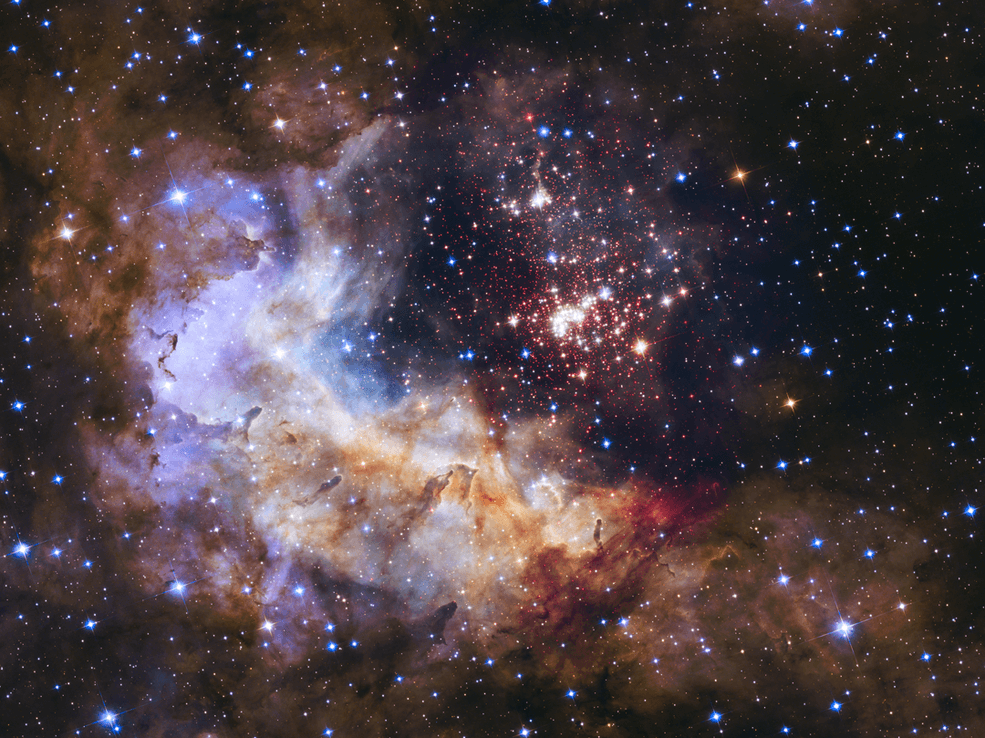 The brilliant tapestry of young stars flaring to life resembles a glittering fireworks display in this Hubble Space Telescope image. The sparkling centerpiece of this fireworks show is a giant cluster of thousands of stars called Westerlund 2. The cluster resides in a raucous stellar breeding ground known as Gum 29, located 20,000 light-years away from Earth in the constellation Carina. Hubble's Wide Field Camera 3 pierced through the dusty veil shrouding the stellar nursery in near-infrared light, giving astronomers a clear view of the nebula and the dense concentration of stars in the central cluster. The cluster measures between six light-years and 13 light-years across. (Image: NASA, ESA, the Hubble Heritage Team (STScI/AURA), A. Nota (ESA/STScI) and the Westerlund 2 Science Team)
