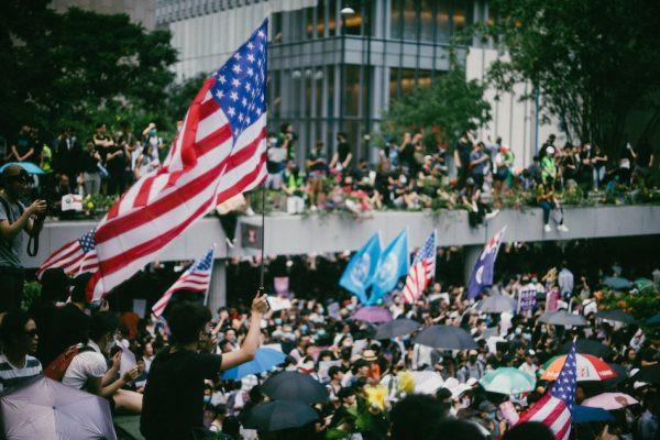 Pro-democracy protesters waving U.S. flags during a march to Hong Kong's U.S. Consulate to call for help from the Trump administration in ending a three-month confrontation with the pro-Beijing Hong Kong government, September 8, 2019. (Image: Joseph Chan/Unsplash)