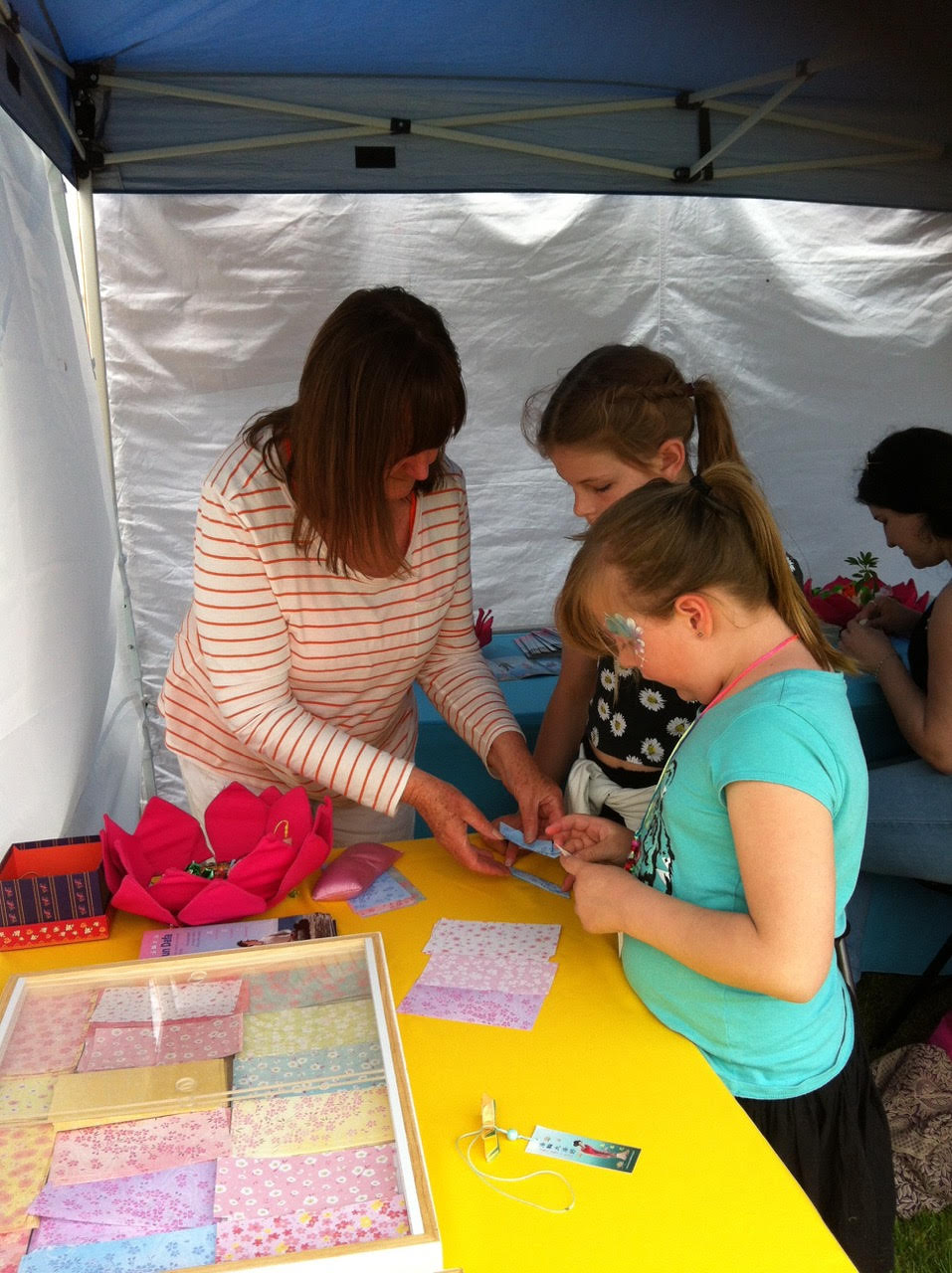 Janine teaching how to make a paper lotus flower with children choosing bright coloured origami paper. Image: Janine Rankin