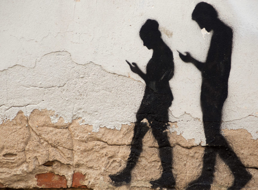 Man and Woman Walking with mobile phone, neck bent.