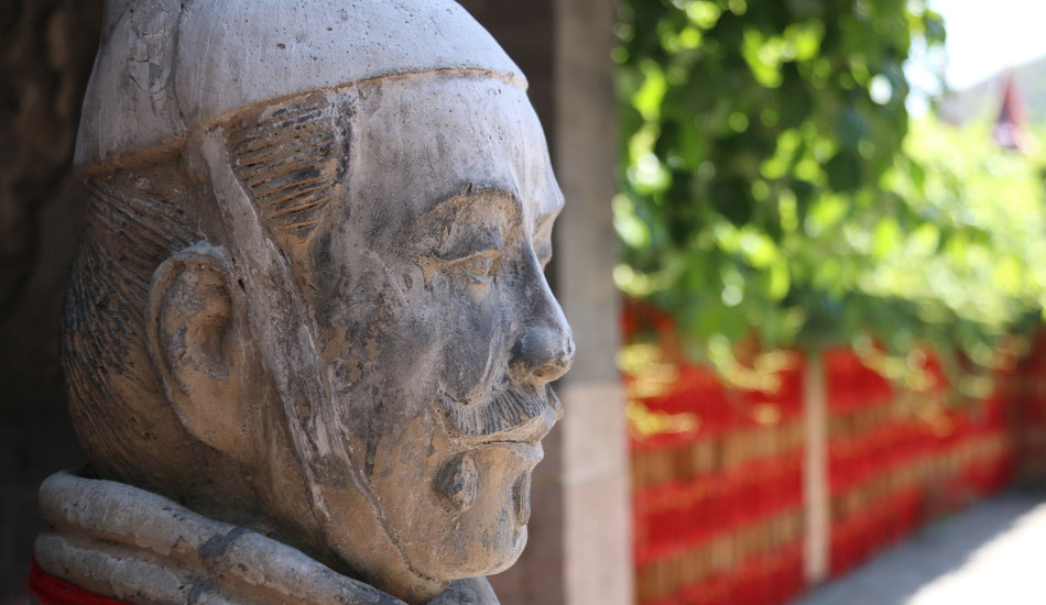 Statue of a Chinese warrior in a courtyard.