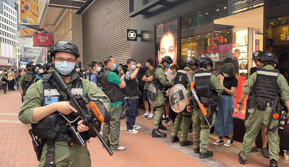 Hong Kong police surround citizens standing in front of a store.