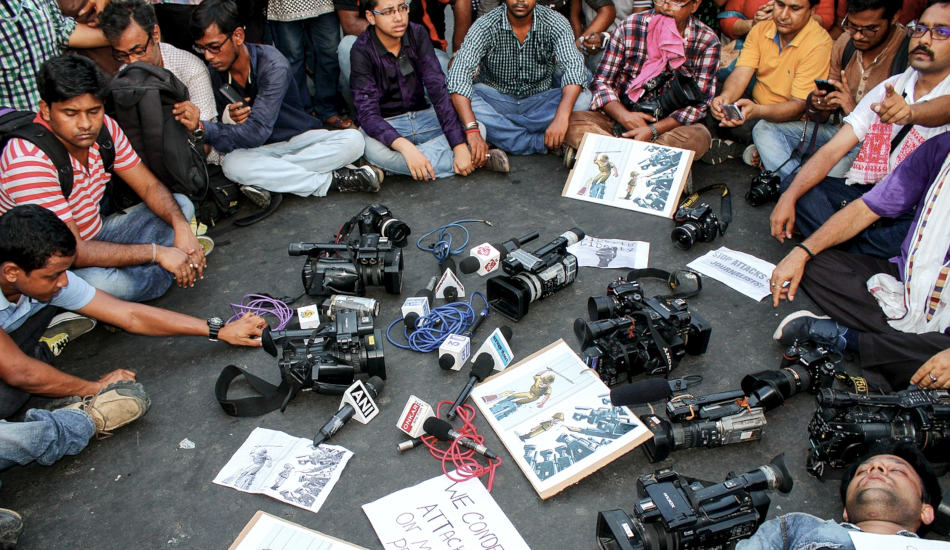 A group of journalists in India sit in a circle around a pile of cameras and microphones.