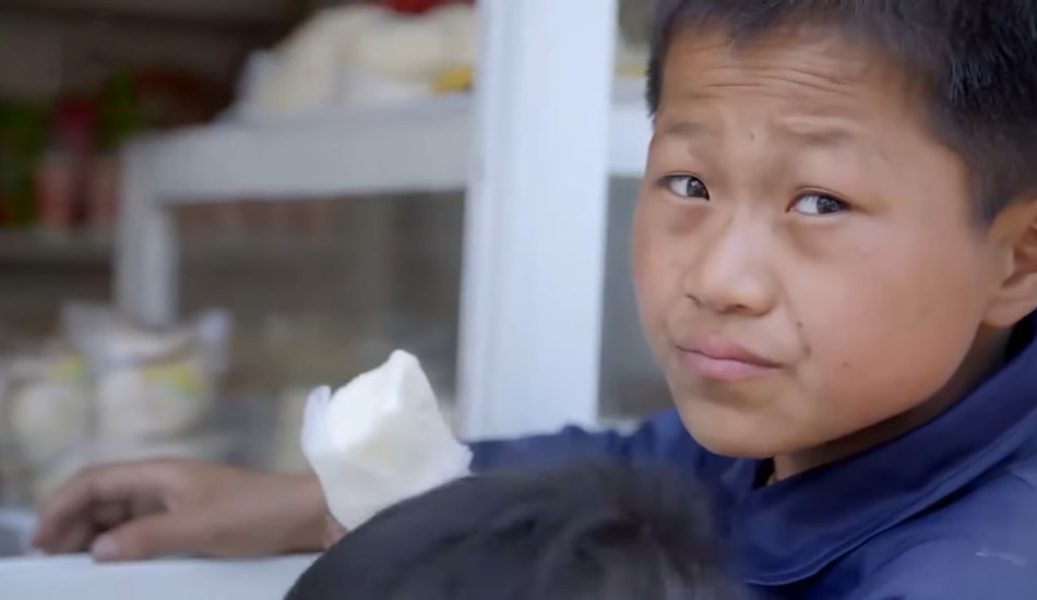A North Korean boy with a dirty face holding a snack.