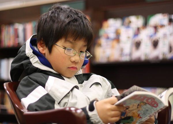 A young boy reading the manga Black Cat