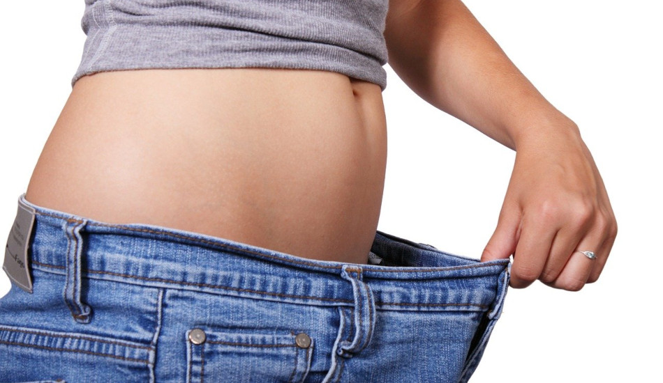 Skinny woman showing she has lost weight by pulling her jeans away from her belly.