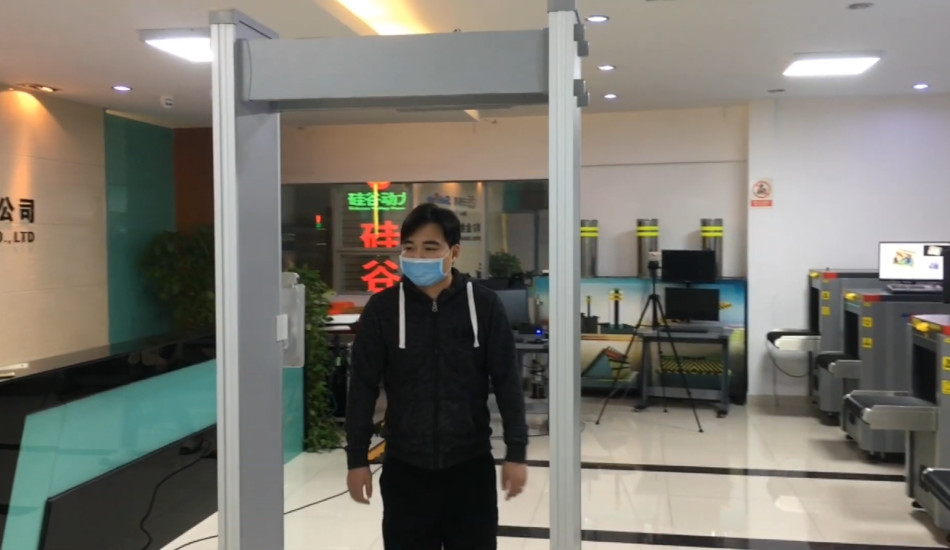 Chinese man wearing mask passes through metal detector equiped with facial recognition.
