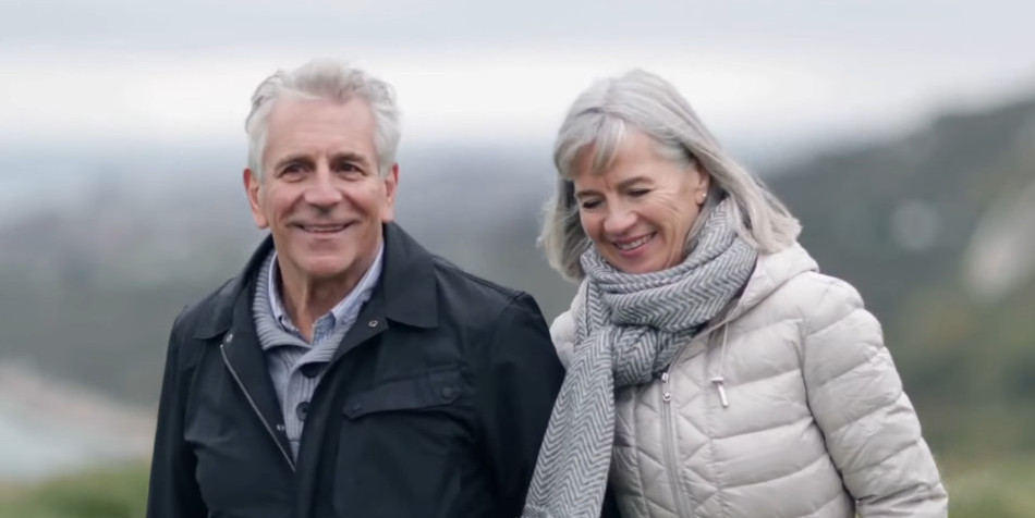 A gray-haired couple walking arm in arm.