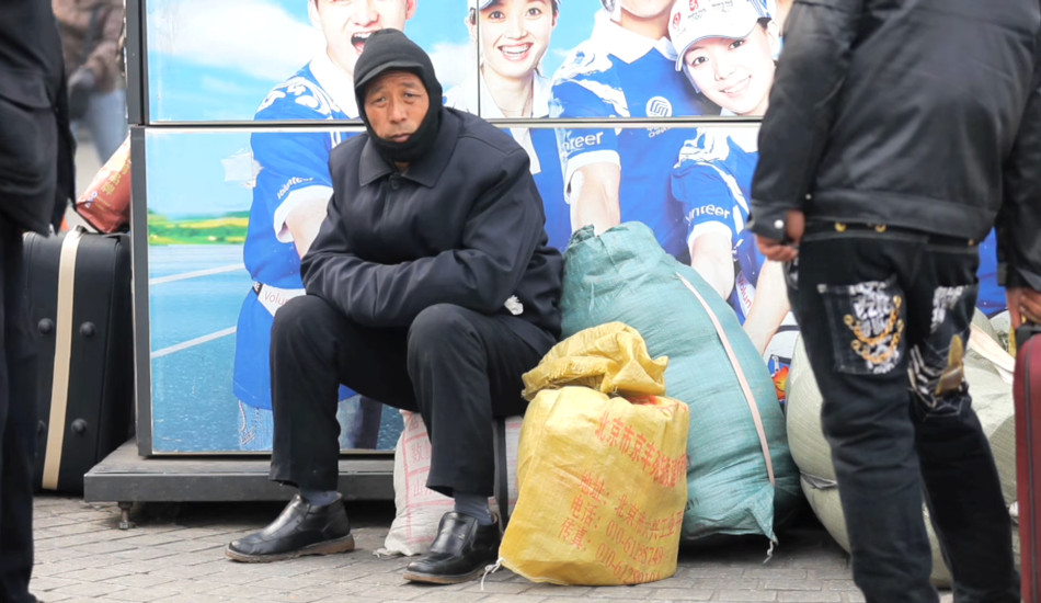 Migrant worker sitting outside Beijing railway station.