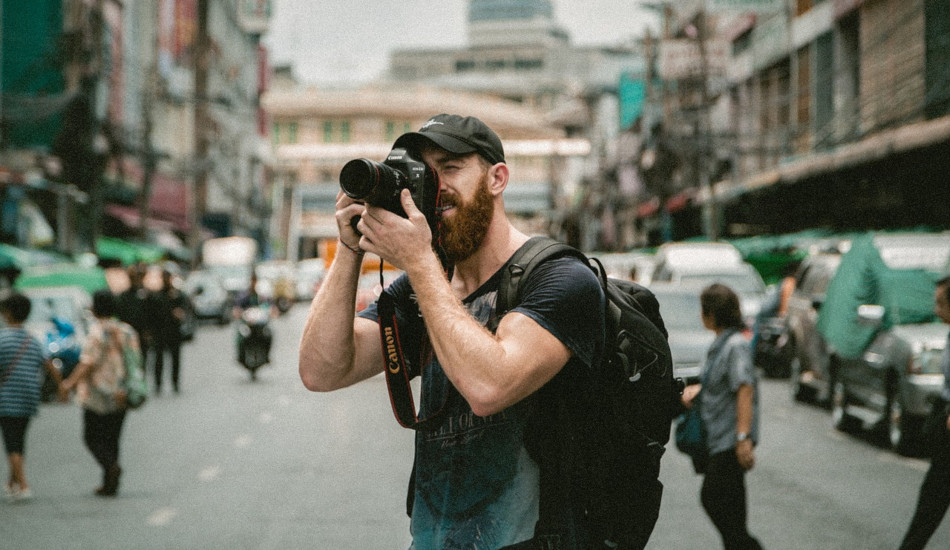 A man stands in the middle of the street to take a photo.