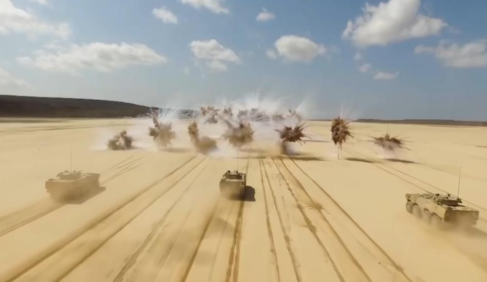 Three tanks firing weapons.