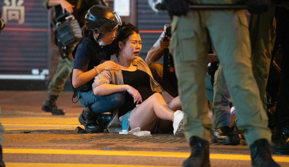 A young woman in Hong Kong sitting on the street after being injured.