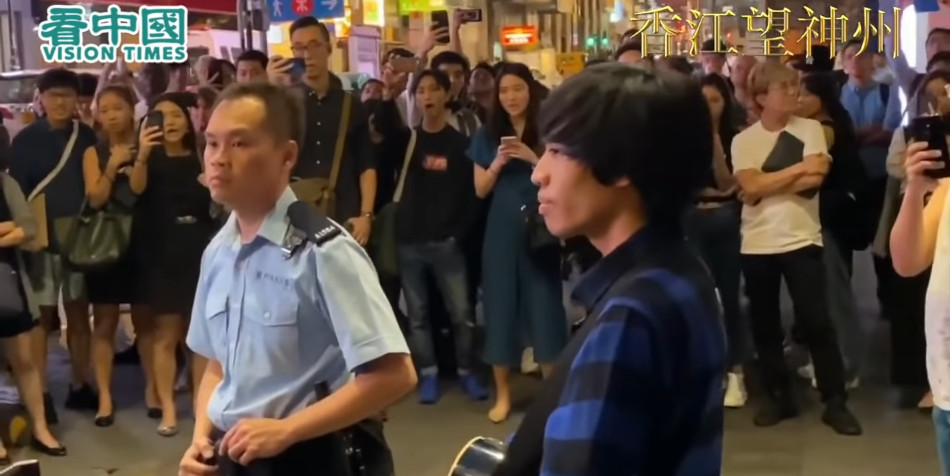 A street singer holds his guitar while confronted with a Hong Kong police officer.
