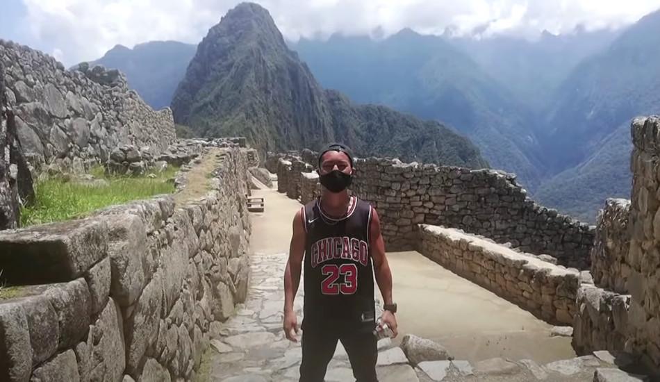 Japanese tourist Jesse Katayama standing amidst the ruins at Machu Picchu.