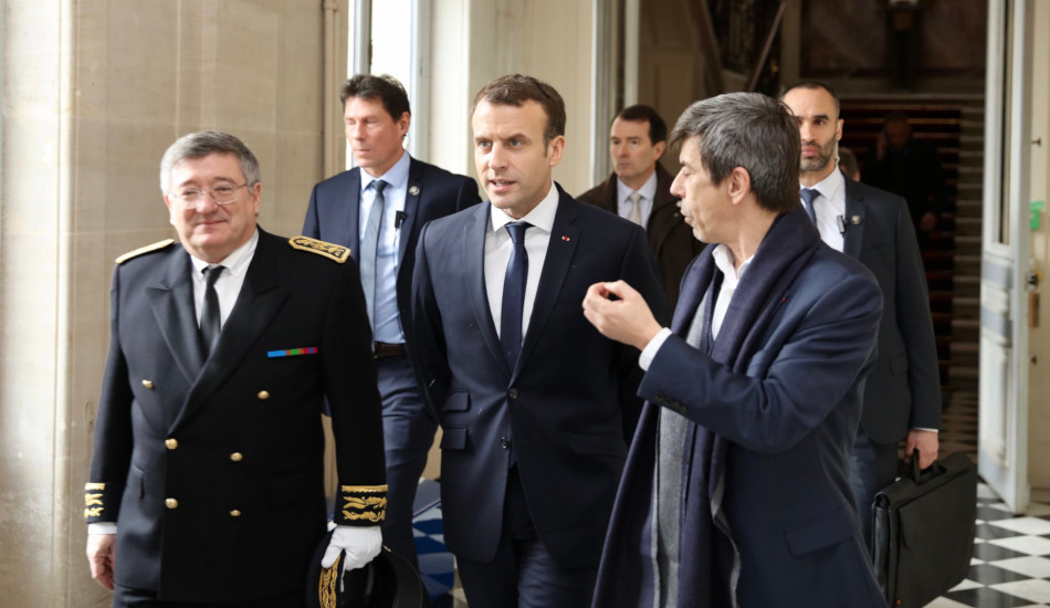 French President Macron walking with his advisors.