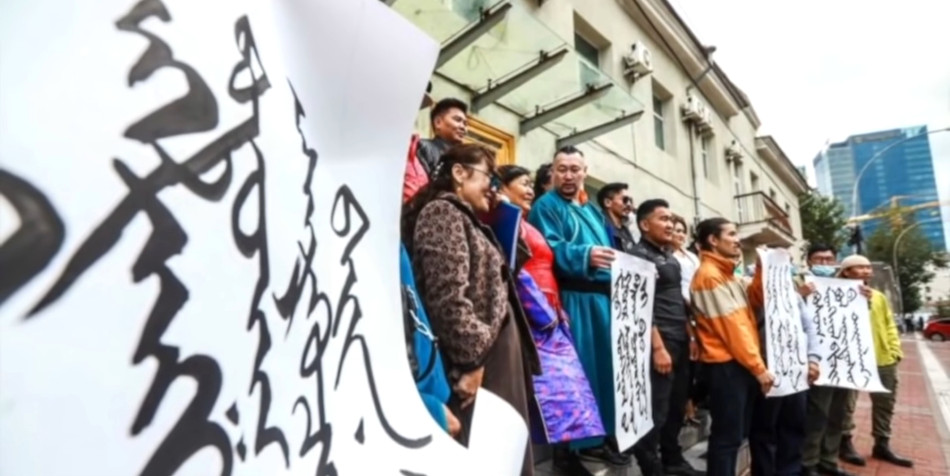 People holding protest signs written in the Mongolian language.