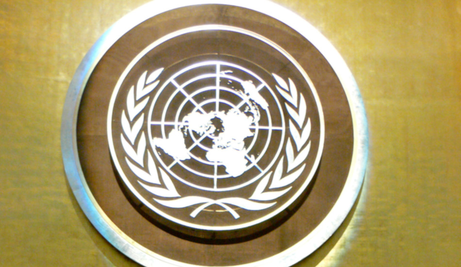 The United Nations logo, white on a gold background.