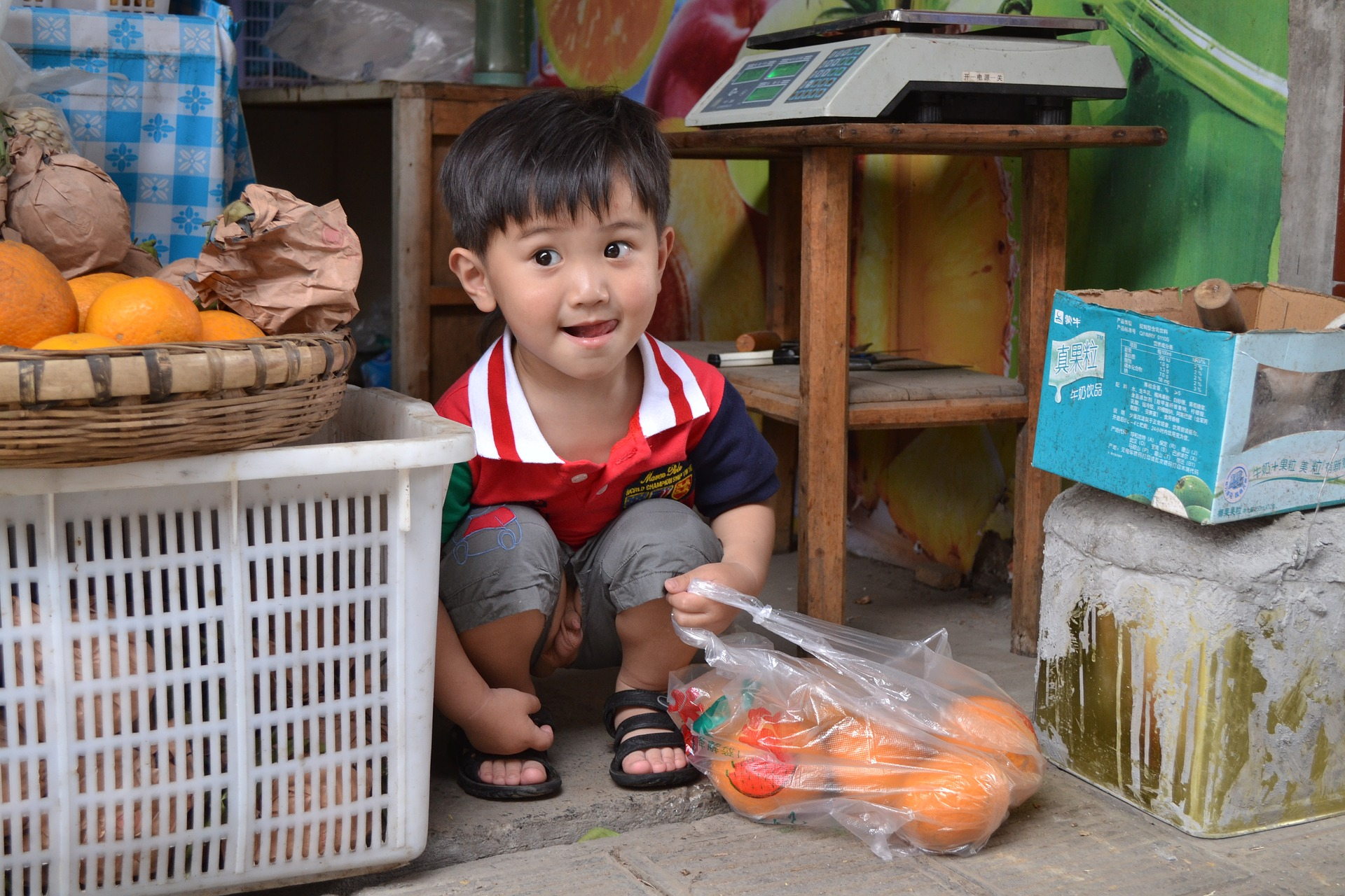 An Asian boy squatting on the ground and holding a bag of oranges.