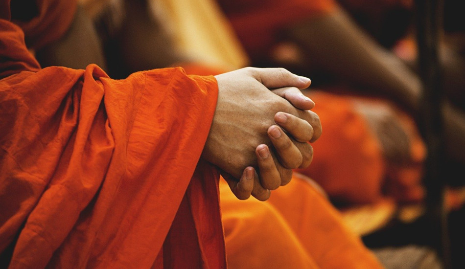 Closeup shot of a Buddhist monk's clasped hands.