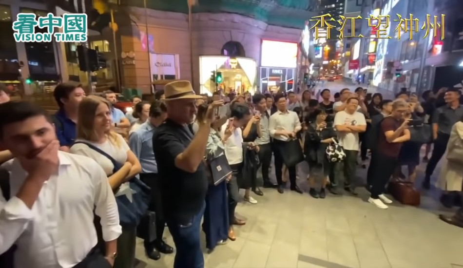 """A crowd gathers to listen to a street performer sing """"Glory to Hong Kong""""."""