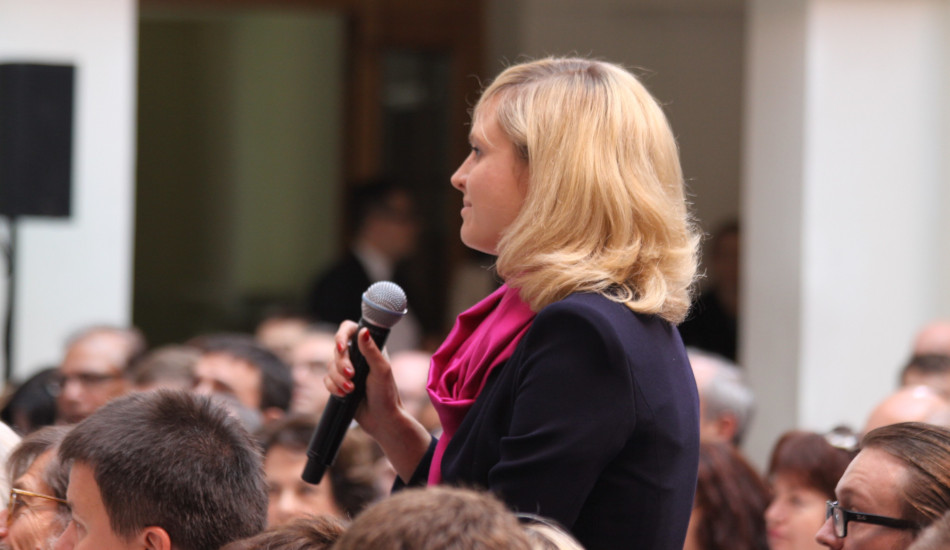 A woman in the audience at a debate stands with a microphone to ask a question.