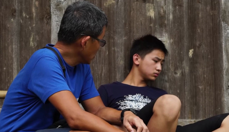 A man talks to a depressed Chinese youth.