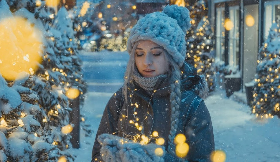 A girl standing next to a Christmas tree in the snow holding lights.