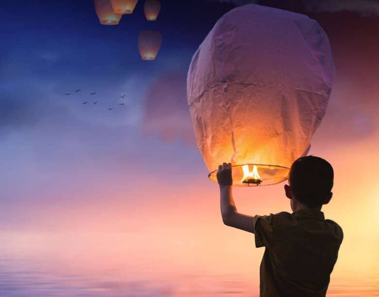 A boy launches a flying lantern into the air.