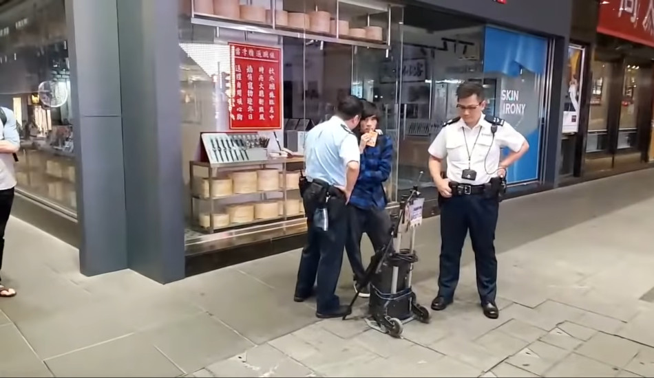 A street singer listens calmly to an angry police officer in Hong Kong.