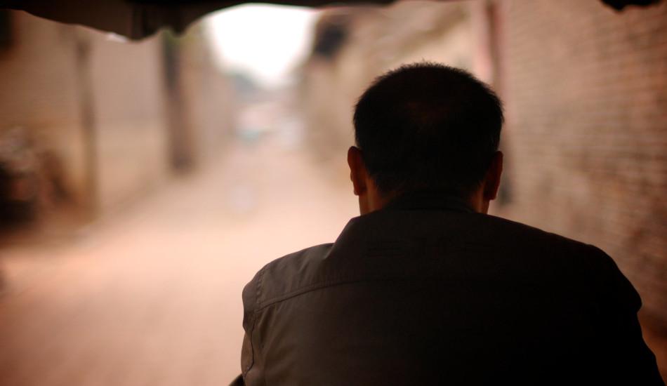 A man driving a cart through an alley in China.