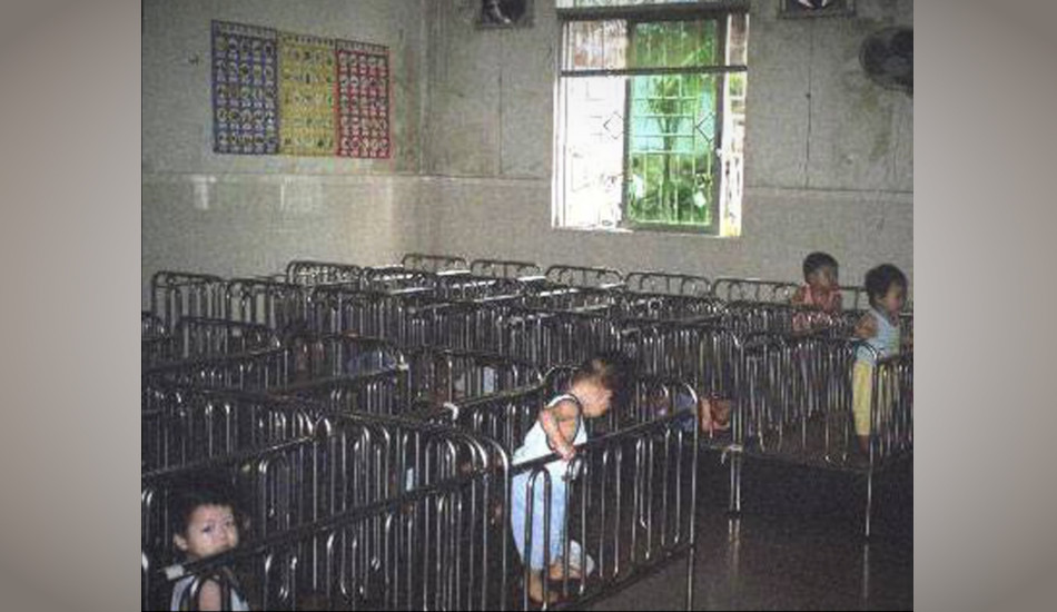 Rows of metal cribs crowded together with Chinese children in them.