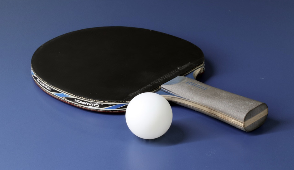 A ping pong ball sitting next to a paddle on a ping pong table.