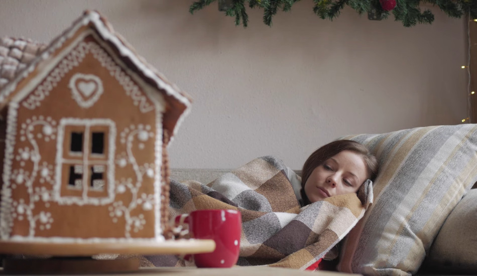 Sad woman under a blanket with a gingerbread house in the foreground.