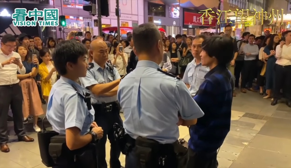 A singing protester is surrounded by four police officers.