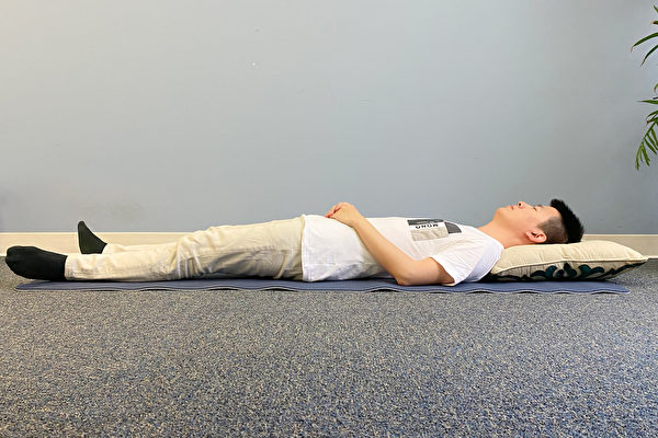 A man sleeping on his back with hands resting on the abdomen.
