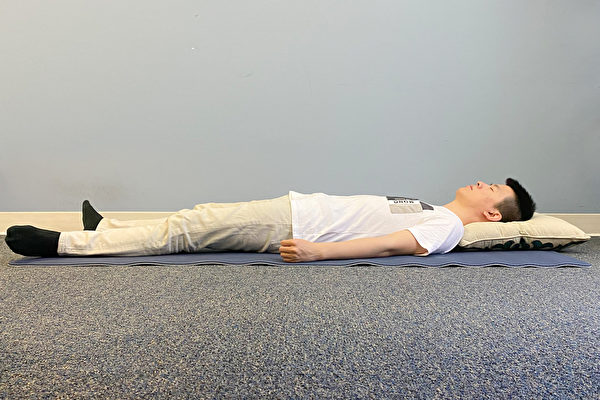 A man sleeping on his back with arms at the side of his body.