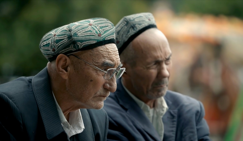 Two Uyghur men sitting side by side.