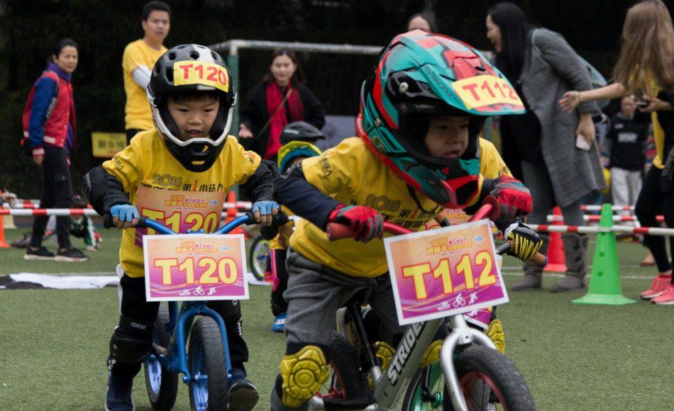 Asian boys riding balance bikes.