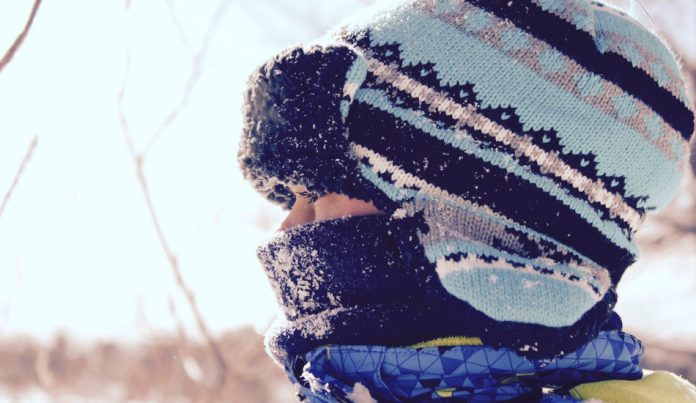 A child bundled up outside in the snow.