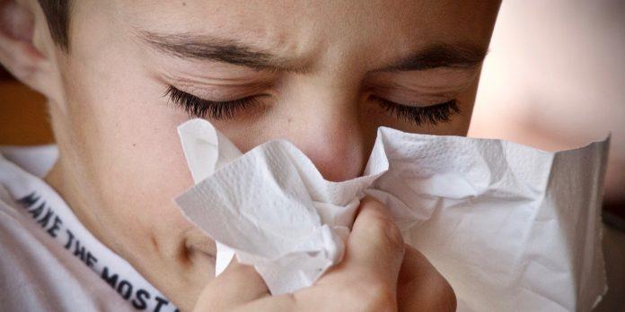 Boy sneezing into a tissue.