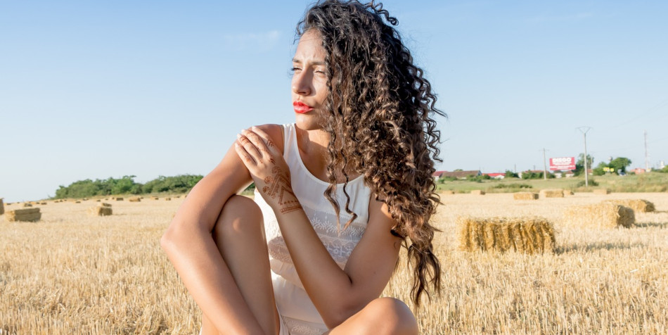 Woman wearing a white tank top sits on a straw bale in a field.