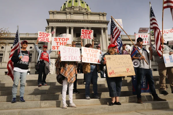 protesters in pennsylvania hold up signs to protest alleged voter fraud in the us 2020 election. georgia is going to have a hand recount